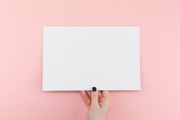 Frauenhände mit leerem blatt des papiers a4 Premium Fotos