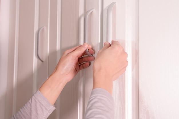 Frauenhände öffnen schrank- / schranktür, weiße holztür Premium Fotos