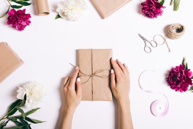 Frauenhände sind verpackte weihnachtsgeschenke auf einem weißen hintergrund Premium Fotos