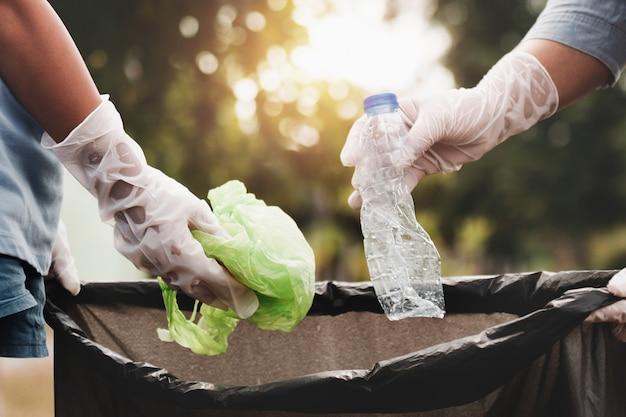 Frauenhand, die abfallplastik für das säubern am park aufhebt Premium Fotos