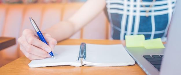 Frauenhand, die an einem computer arbeitet und auf einen notizblock mit einem stift in das büro schreibt. Premium Fotos