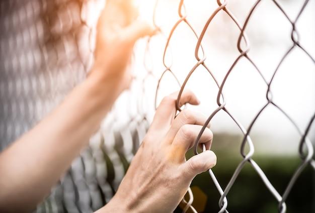 Frauenhand, die an kettengliedzaun für erinnert sich, menschenrechtstag hält Premium Fotos