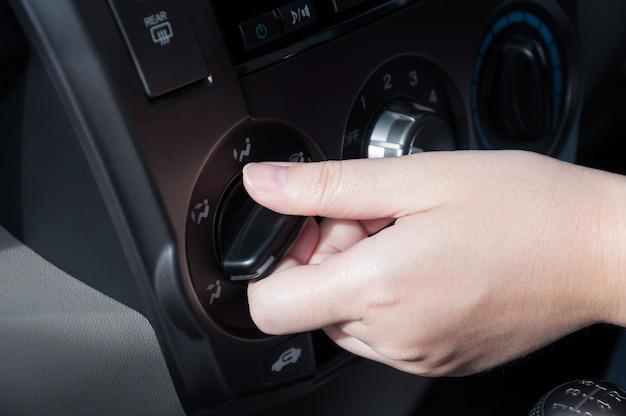 Frauenhand, die autoklimaanlage einschaltet Premium Fotos