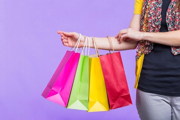 Frauenhand, die bunte einkaufstasche auf purpurrotem hintergrund hält Kostenlose Fotos