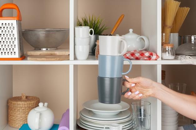 Frauenhand, die dishwarestücke vom regal in der küche nimmt Premium Fotos
