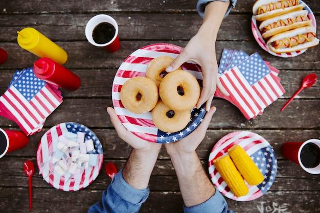 Frauenhand, die donut nimmt Kostenlose Fotos