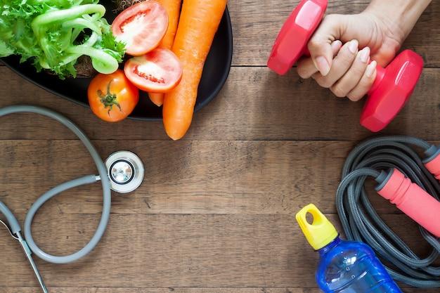 Frauenhand, die dummkopf, gesunde nahrungsmittel und eignungsausrüstungen auf holz hält Premium Fotos