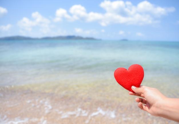 Frauenhand, die ein rotes herz auf dem strand mit unscharfem hintergrund des meeres und des blauen himmels hält. liebe konzept. Premium Fotos