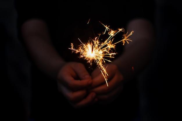 Frauenhand, die eine brennende wunderkerze hält Premium Fotos