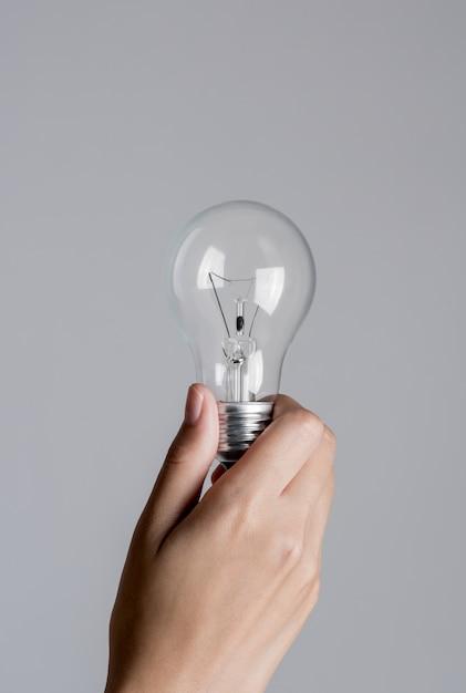 Frauenhand, die eine glühlampe auf weißem hintergrund hält Premium Fotos