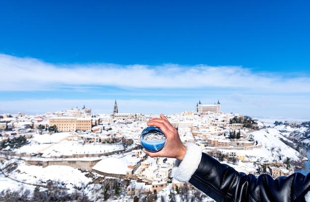 Frauenhand, die eine kristallkugel hält. panoramablick auf die stadt toledo im hintergrund. Premium Fotos