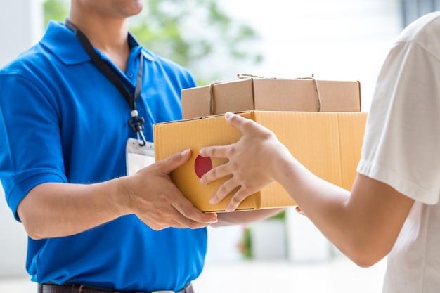 Frauenhand, die eine lieferung von kästen vom lieferboteen annimmt Premium Fotos