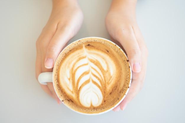 Frauenhand, die eine weiße kaffeetasse hält. kaffee ist eine latte. Premium Fotos