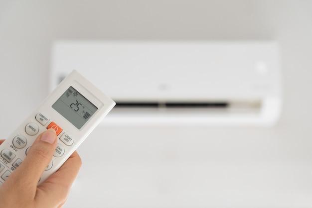 Frauenhand, die fernbedienung gerichtet auf die klimaanlage hält Premium Fotos