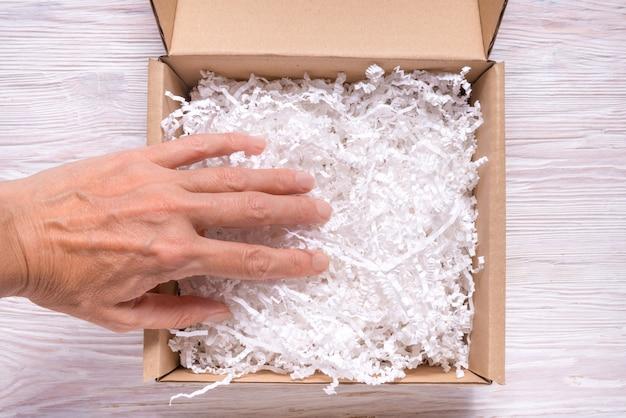 Frauenhand, die geschredderten papierfüller zum pappkarton setzt Premium Fotos