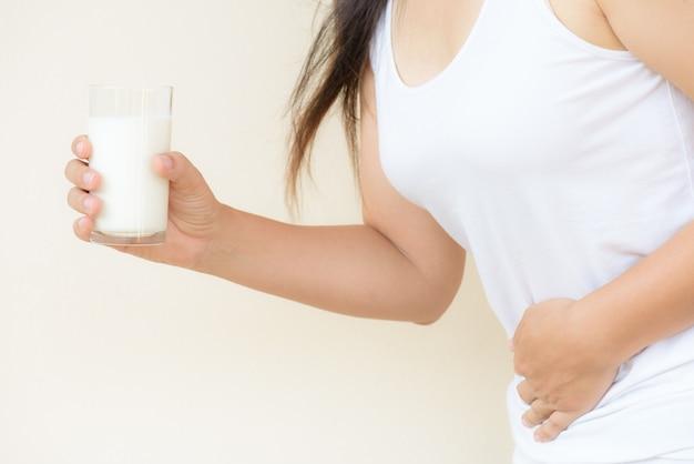 Frauenhand, die glas milch hat schlechten magenschmerz hält. Premium Fotos