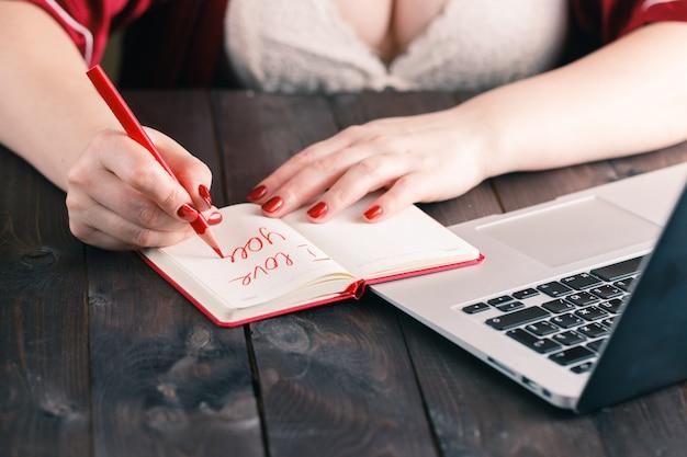 Frauenhand, die herz zeichnet und schreibt, ich liebe dich Premium Fotos