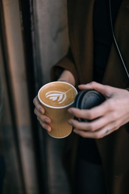 Frauenhand, die kaffee mit latte art auf einem grauen teller von oben erreicht. holztisch im hipster-café. vintage farbfiltereffekt. Kostenlose Fotos