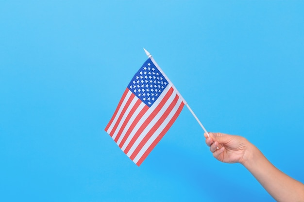 Frauenhand, die kleine amerikanische flagge auf blauem hintergrund hält. platz für text. Premium Fotos