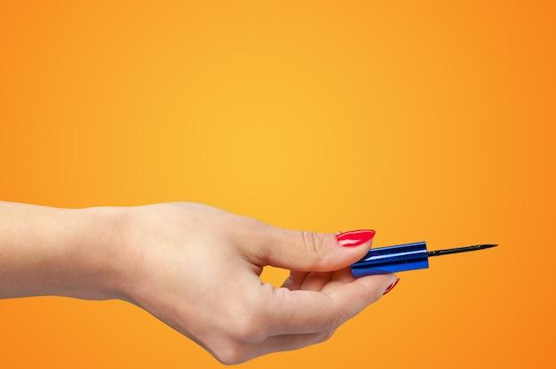 Frauenhand, die kosmetisches werkzeug lokalisiert auf farbhintergrund hält Premium Fotos