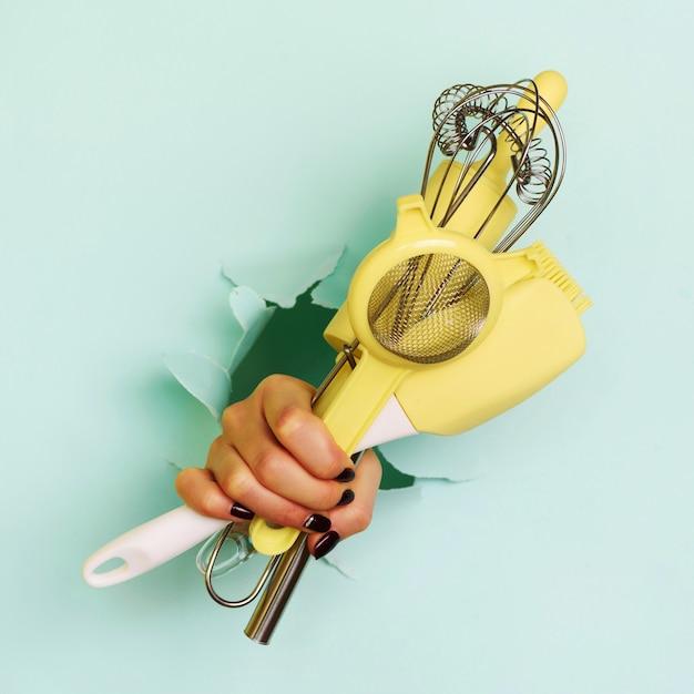 Frauenhand, die küchengeräte auf blauem hintergrund hält Premium Fotos