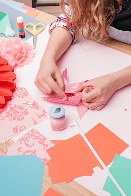 Frauenhand, die polka punktiertes origami feuerrad bildet Kostenlose Fotos