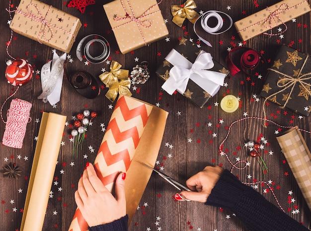 Frauenhand, die rolle des kraftpapiers mit scheren für den schnitt der verpackungsweihnachtsgeschenkbox hält Kostenlose Fotos