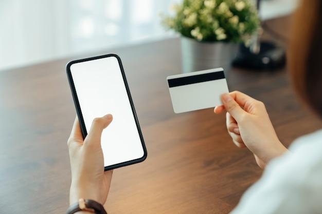 Frauenhand, die smartphone verwendet und kreditkarte mit zahlung online auf handy hält. Premium Fotos