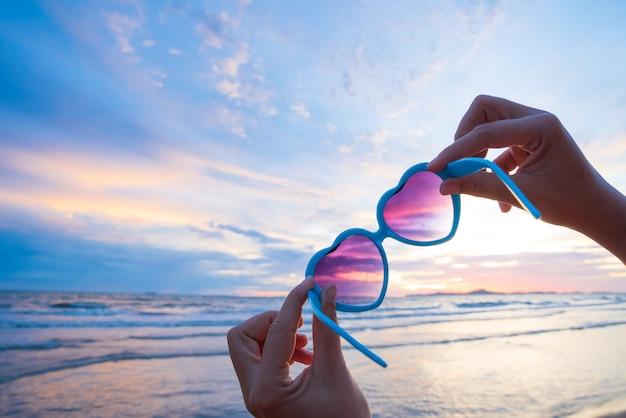 Frauenhand, die sonnenbrille in der herzform während des sonnenuntergangs hält. Premium Fotos