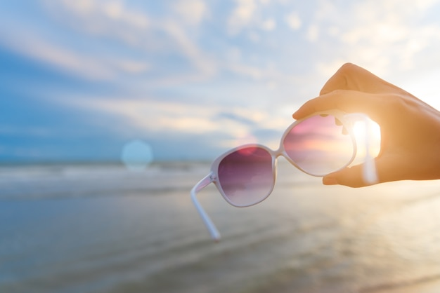 Frauenhand, die sonnenbrille über meer während des sonnenuntergangs für sommerkonzept hält. Premium Fotos