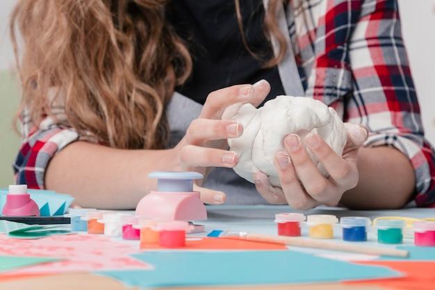 Frauenhand, die weißen lehm für handwerk knetet Kostenlose Fotos
