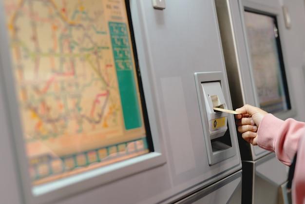 Frauenhand fügt karte ein, um u-bahnfahrkarte in der maschine zu kaufen. Premium Fotos