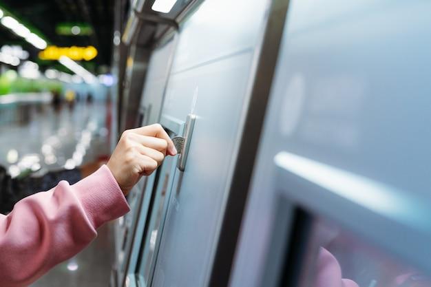 Frauenhand fügt münze ein, um u-bahn-bahnfahrkarte in der maschine zu kaufen. Premium Fotos