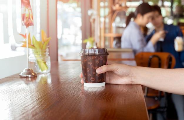 Frauenhand hält einen papiertasse kaffee zum wegnehmen. Premium Fotos