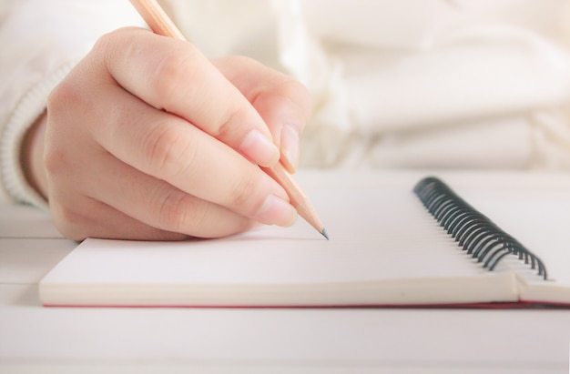 Frauenhand mit bleistiftschreiben auf weißem notizbuch. Premium Fotos