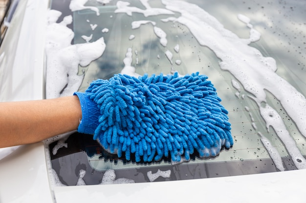 Frauenhand mit dem blauen mikrofasergewebe, das modernes auto des rückspiegels wäscht oder automobil säubert. Premium Fotos