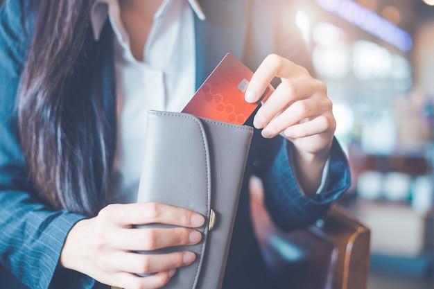 Frauenhand mit einer kreditkarte zog sie die karte aus ihrer brieftasche. Premium Fotos