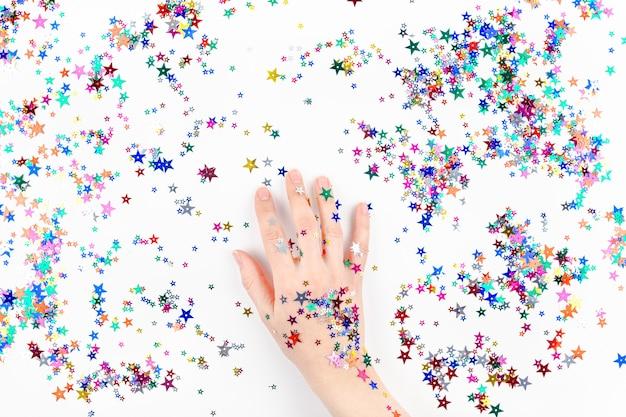 Frauenhand mit festlichen farbsternkonfettis Premium Fotos