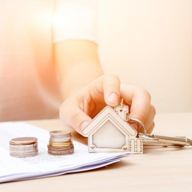 Frauenhand mit geld und grundstellungstaste. unterzeichneter vertrag und schlüssel des eigentums mit dokumenten. konzept für das immobiliengeschäft. Premium Fotos