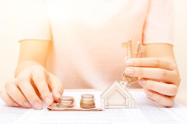 Frauenhand mit geld und hauptschlüssel. signierter vertrag und schlüssel der immobilie mit dokumenten. konzept für das immobiliengeschäft. Premium Fotos