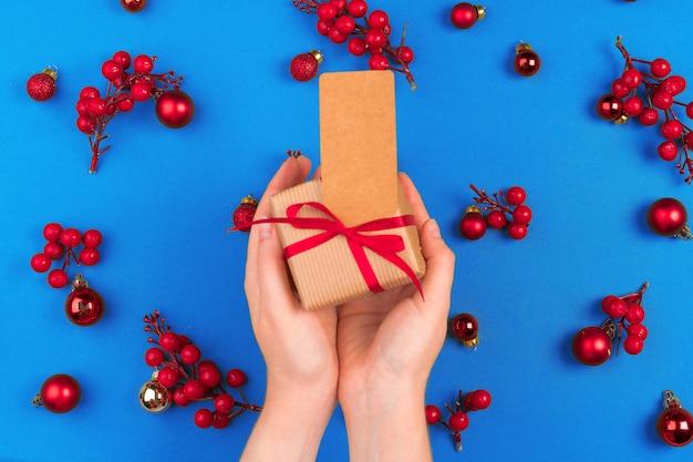 Frauenhand mit geschenk auf verziertem weihnachtshintergrund Premium Fotos
