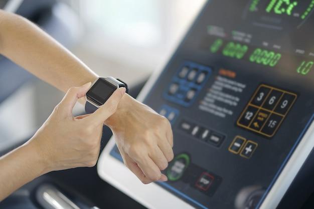 Frauenhand mit intelligenter uhr auf handgelenk, tragbares eignungsgerät, sportlicher läufer, der den übungslauf innen tut und gewichtsverlust mit der maschine aerob nimmt. gesunder sport cardio stark. Premium Fotos