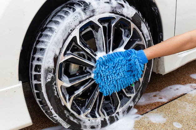 Frauenhand mit modernem auto des blauen mikrofasergewebes waschendem rad oder reinigungsautomobil. Premium Fotos