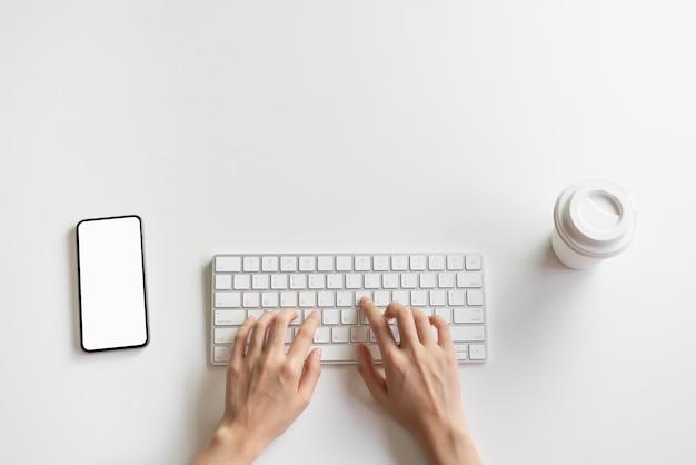 Frauenhand schreiben tastatur und smartphone, kaffeetasse auf dem schreibtisch. Premium Fotos