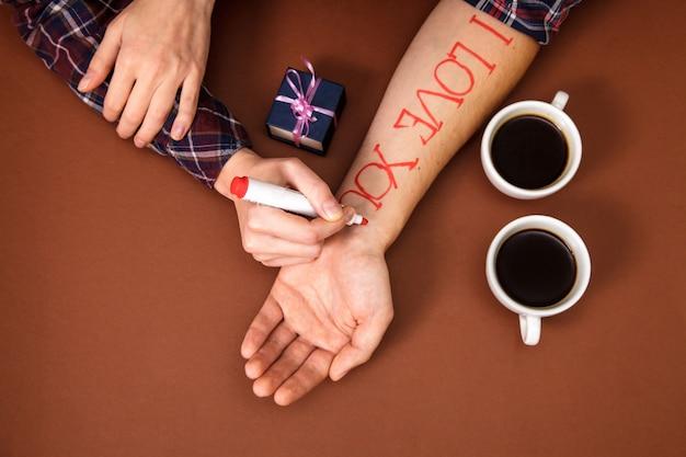 Frauenhand schreibt rote buchstaben ich liebe dich auf männerhand in der nähe von zwei tassen kaffee auf braun. Premium Fotos