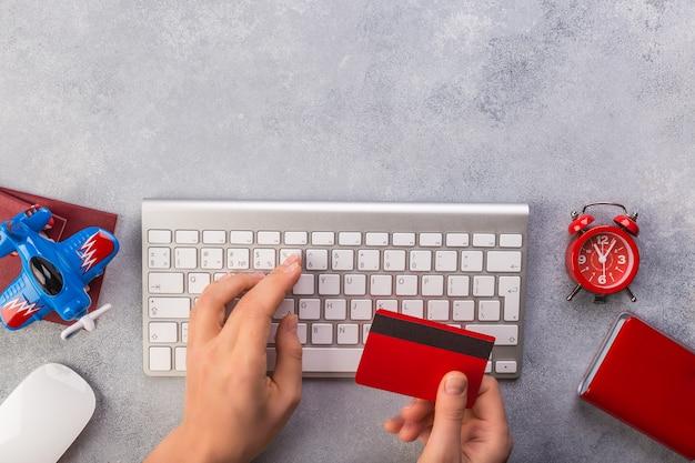 Frauenhand schreibt tastatur und nimmt kreditkarte nahe kleiner flugzeuguhr und -pässen Premium Fotos