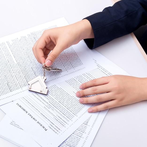 Frauenhand und grundstellungstaste. unterzeichneter vertrag und schlüssel des eigentums mit dokumenten. Premium Fotos