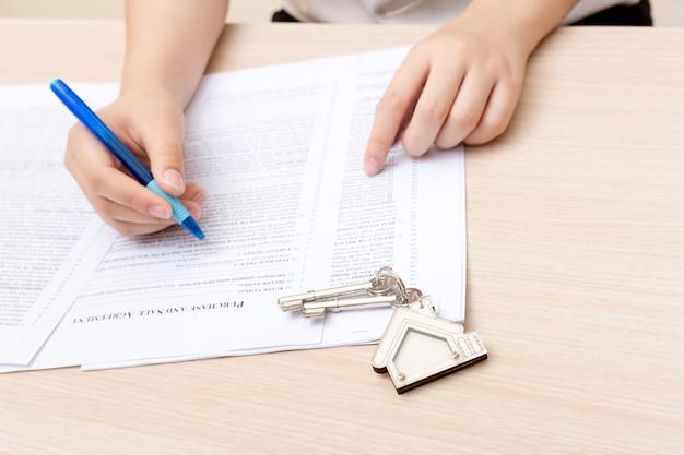 Frauenhand und hauptschlüssel. signierter vertrag und schlüssel der immobilie mit dokumenten. Premium Fotos