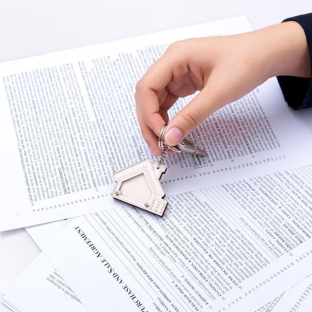 Frauenhand und hauptschlüssel. unterschriebener vertrag und schlüssel der immobilie mit dokumenten. konzept für echte e Premium Fotos
