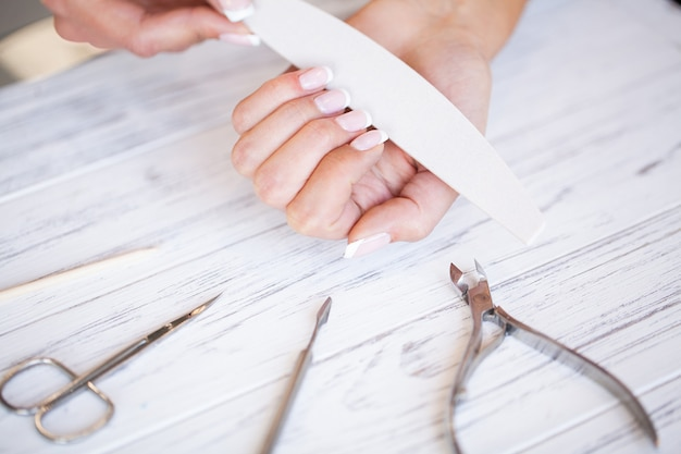 Frauenhandpflege. nahaufnahme von den schönen weiblichen händen, die badekurort-maniküre am schönheits-salon haben. kosmetiker filing clients healthy naturnägel mit nagelfeile. nagelbehandlung Premium Fotos